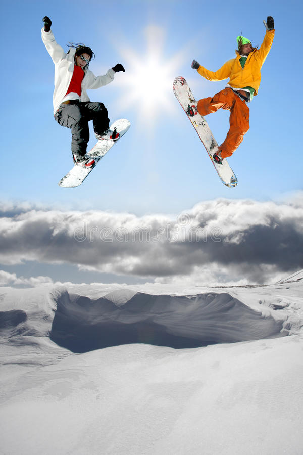 Snowboarders jumping against blue sky stock images