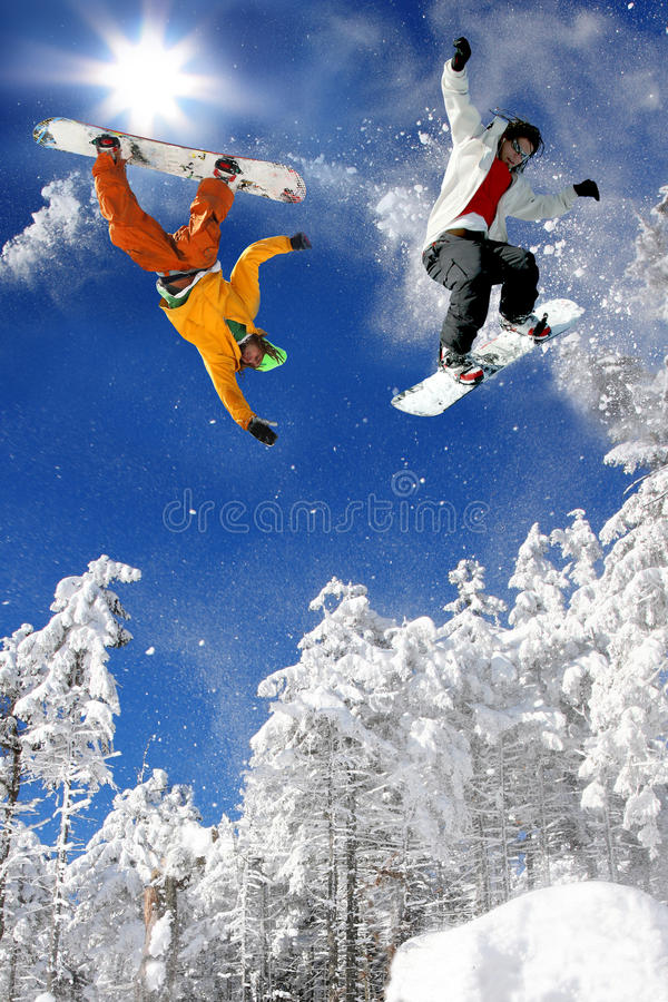 Snowboarders jumping against blue sky stock photos