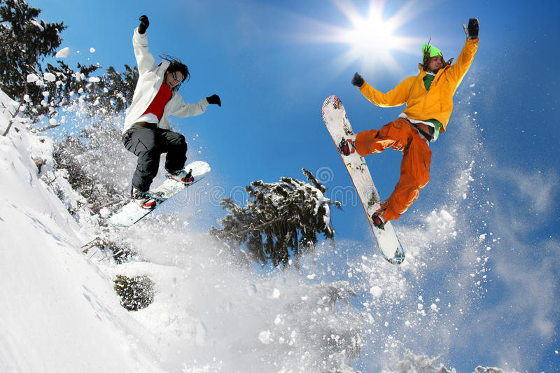 Snowboarders jumping against blue sky royalty free stock photography