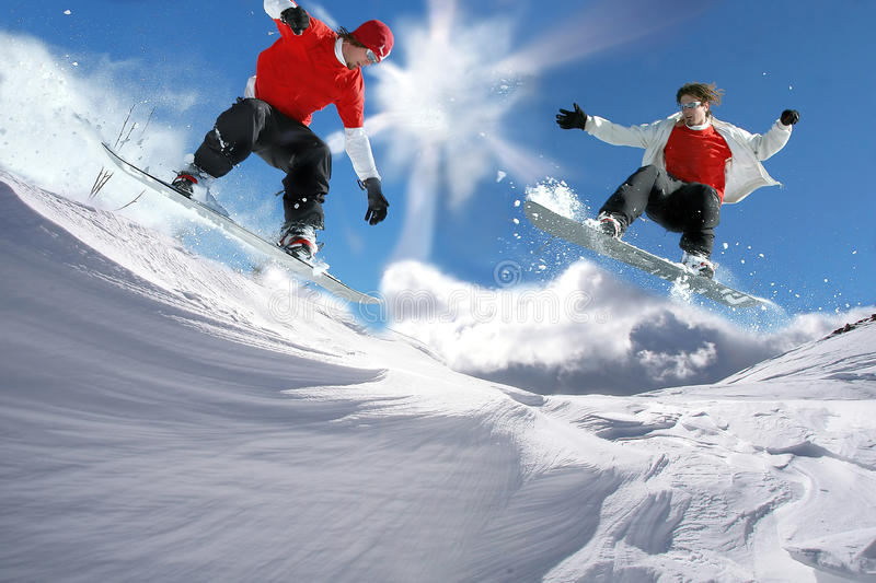 Snowboarders jumping against clear sky stock photo