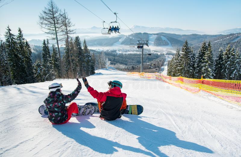 Snowboarders sit on top of ski slope under the lift. Snowboarders sit on the top of the ski slope under the ski lift let`s high five to each other with a stock photos
