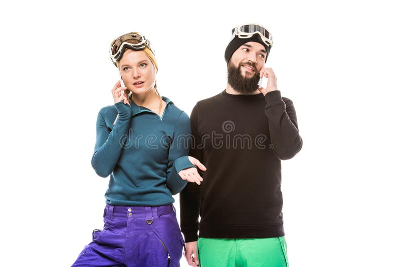Snowboarders talking on smartphones stock photography