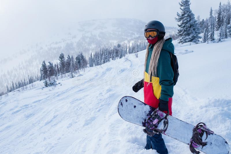 Snowboardervrouw op een sneeuwhelling in de bergen Sport royalty-vrije stock foto