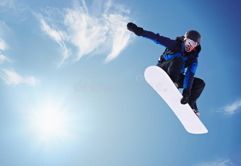 Snowboarding. Snowboarder jumping against blue sky