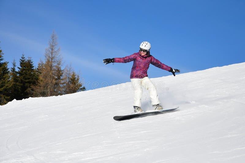 Snowboarding de jeune femme images stock