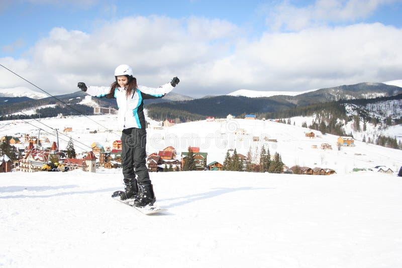 Snowboarding de jeune femme le jour givré d'hiver de pentes images stock