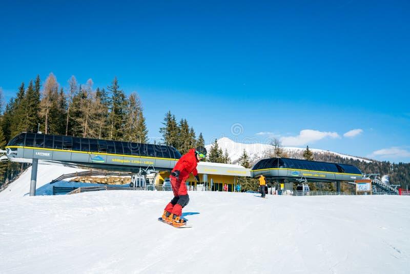 Snowboarding do homem novo abaixo da estância de esqui das montanhas fotos de stock royalty free
