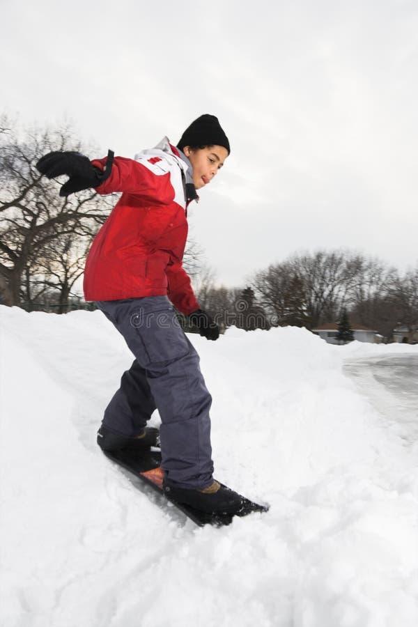 Snowboarding do menino. foto de stock