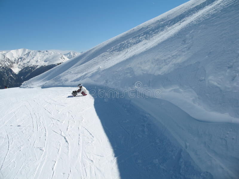 Snowboarding girl sitting on the snow in mountains royalty free stock photos