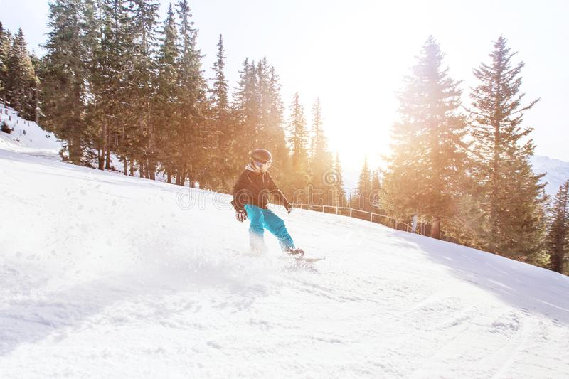 Snowboarding i vinterfjällängar, man med snabb hastighet på snowboard arkivbild