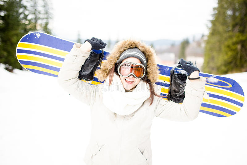 Snowboarding.Young beautiful woman with ski mask holding her snowboard at ski slope Young woman in ski resort. Holding snowboard on her shoulders and smiling royalty free stock photo