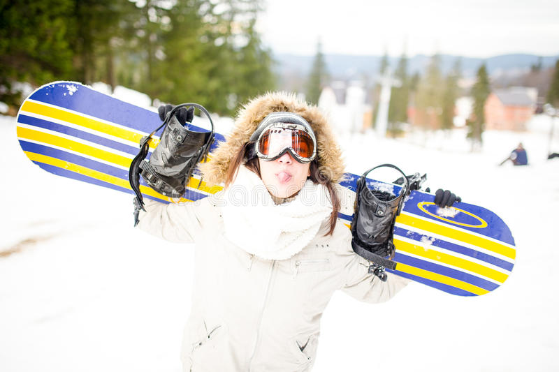 Snowboarding.Young beautiful woman with ski mask holding her snowboard at ski slope Young woman in ski resort. Holding snowboard on her shoulders and smiling stock photography
