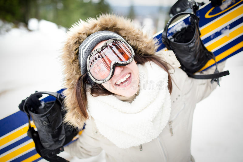 Snowboarding.Young beautiful woman with ski mask holding her snowboard at ski slope Young woman in ski resort. Holding snowboard on her shoulders and smiling stock image