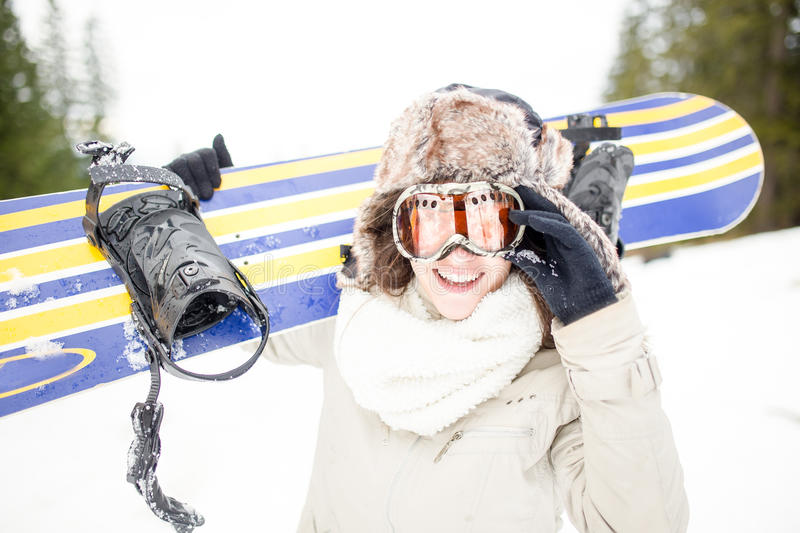 Snowboarding.Young beautiful woman with ski mask holding her snowboard at ski slope Young woman in ski resort. Holding snowboard on her shoulders and smiling royalty free stock images