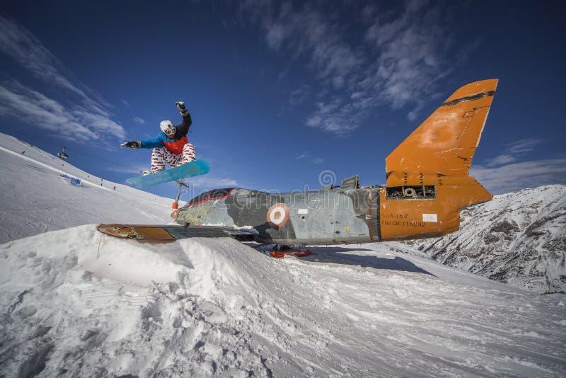 Snowboardingsprung über Fläche in den snowpark Winterbergen stockfotos