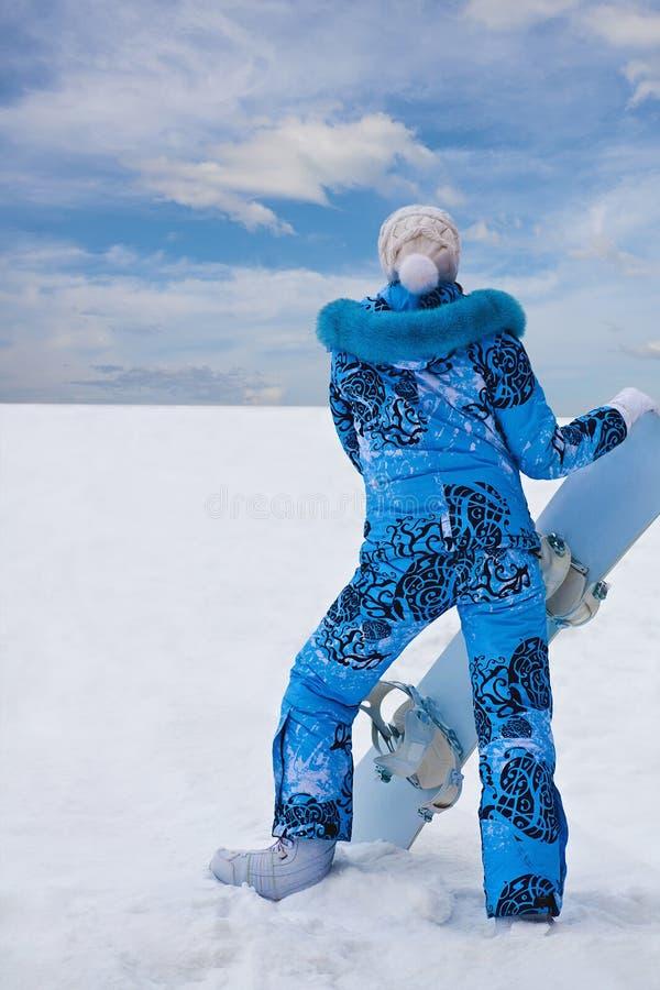 Snowboardmädchen in der blauen Stütze an der Unterseite des Hügels lizenzfreies stockfoto