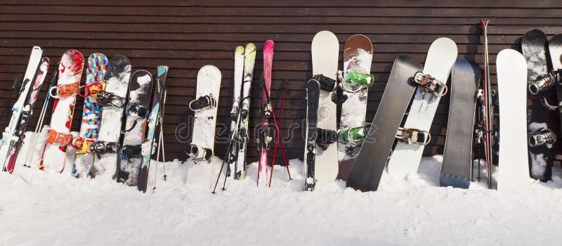 Snowboards och skidar lutat på träväggen arkivbilder