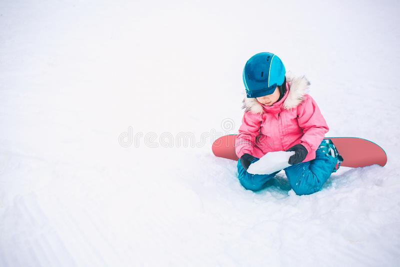 Snowboardvintersport Flicka för liten unge som spelar med snö som bär varm vinterkläder vinter för blåa snowflakes för bakgrund v royaltyfri fotografi
