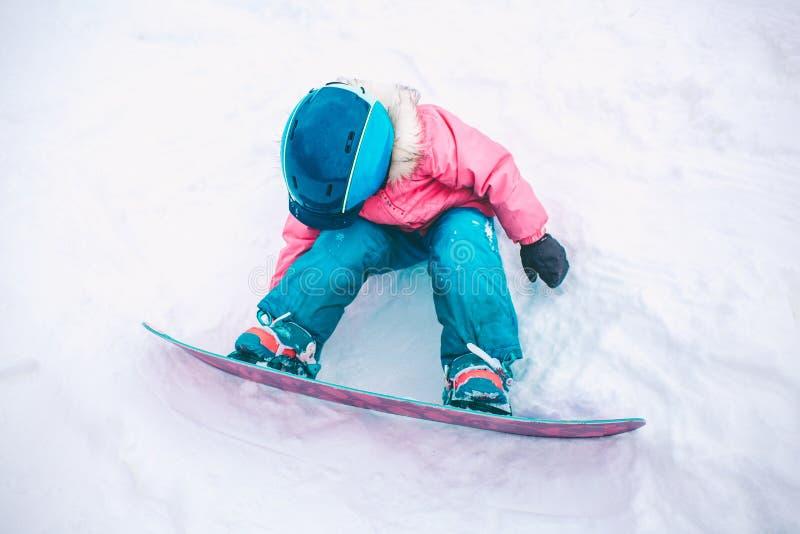 Snowboardvintersport Flicka för liten unge som spelar med snö som bär varm vinterkläder vinter för blåa snowflakes för bakgrund v arkivfoto