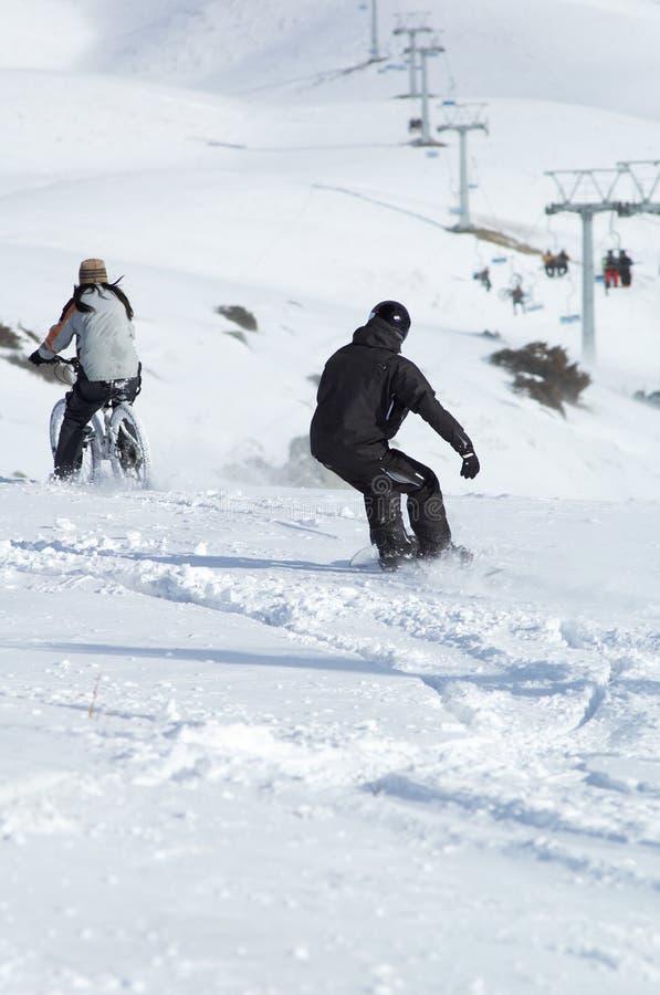 Snowborder et cycliste inclinés image libre de droits