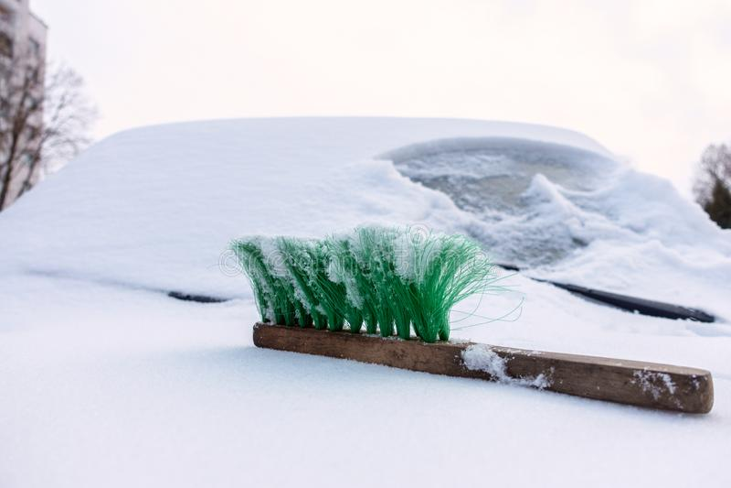 On the snowbound car hood lies a green brush. stock photo