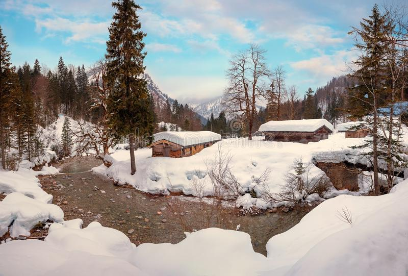 Snowbound huts in the bavarian alps. Snowbound huts at river bend weissach, near kreuth, dreamy winter landscape upper bavaria royalty free stock photography