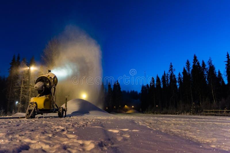 Snowcannon fonctionnant tard produisant la neige photographie stock