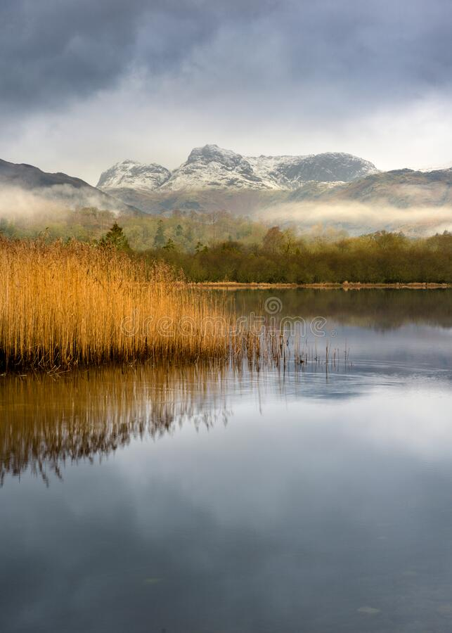 Snowcapped Langdale Pikes From Elterwater in the Lake District. stock photography