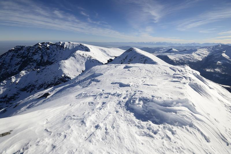 Snowcapped mountain ridge. Scenic view of the alpine arc from the top of the mountain with snowdrifts shaped by the wind and back country ski tracks royalty free stock images