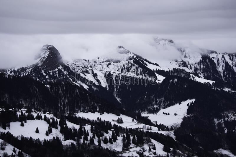 Snowcapped mountains surrounded by clouds in winter. Mountain surrounded by clouds, cloudy sky, snow and trees stock image