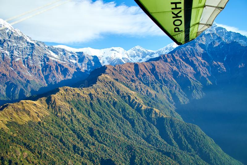 Ultralight aircraft and trees and snowcapped peak at background in the Himalaya mountains, Nepal royalty free stock images