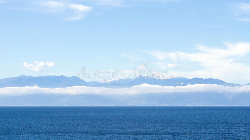 Snowcapped Peloponese Mountains. And white clouds, view across Gulf of Corinth, Greece stock image