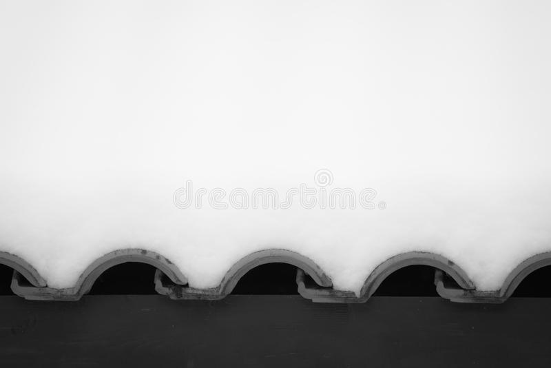 Snowcapped wavy rooftop tiles in black and white royalty free stock photo