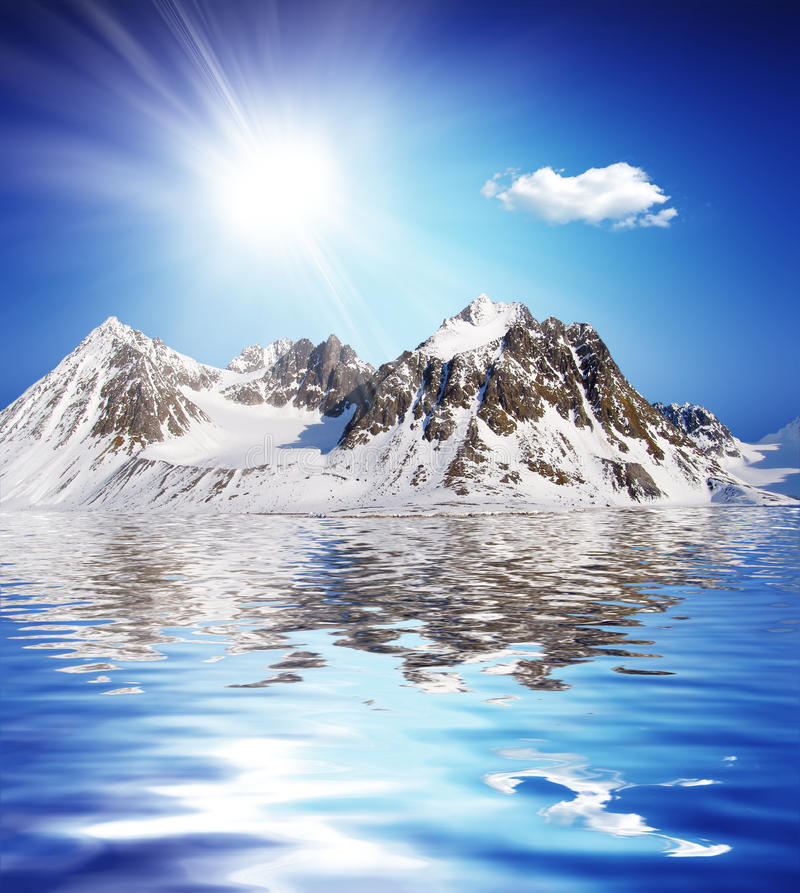 Snowcovered high mountain besides a lake with nice. Sky tropical winter view royalty free stock photos