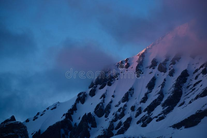 Snowcovered peak in red light. During sunset. Captured in the Swiss alps during the last seconds of a beautiful sunset stock photo