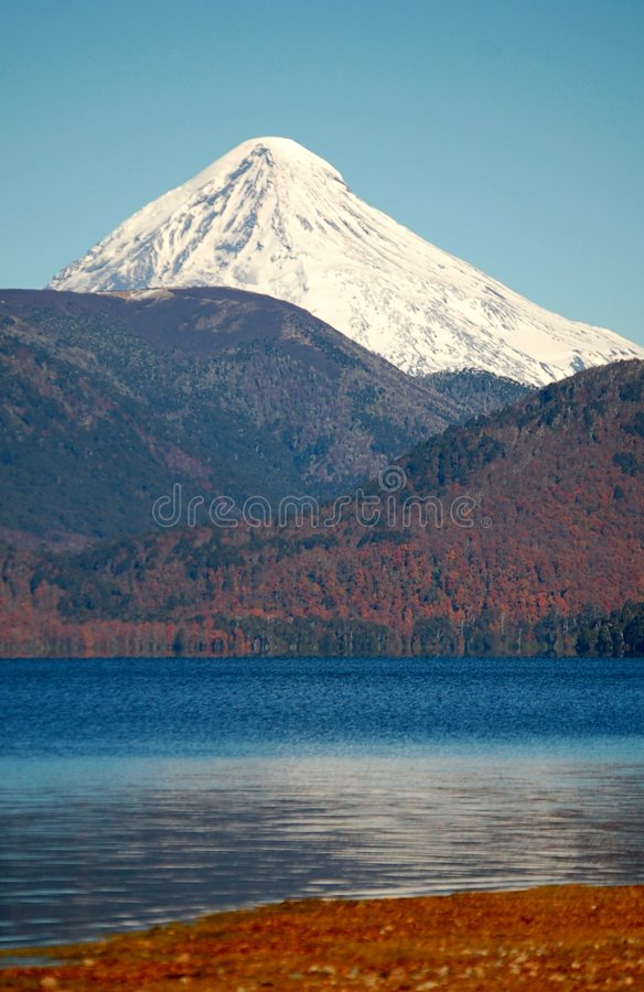 Snowcovered volcano peak in Patagonia. Snowcovered peak of mountain in the background, lake in the foreground. Patagonia landscape royalty free stock image