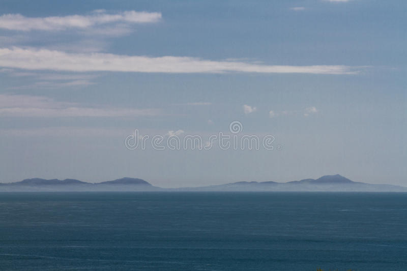 Snowdonia mountains from across water with seam mist. stock photography