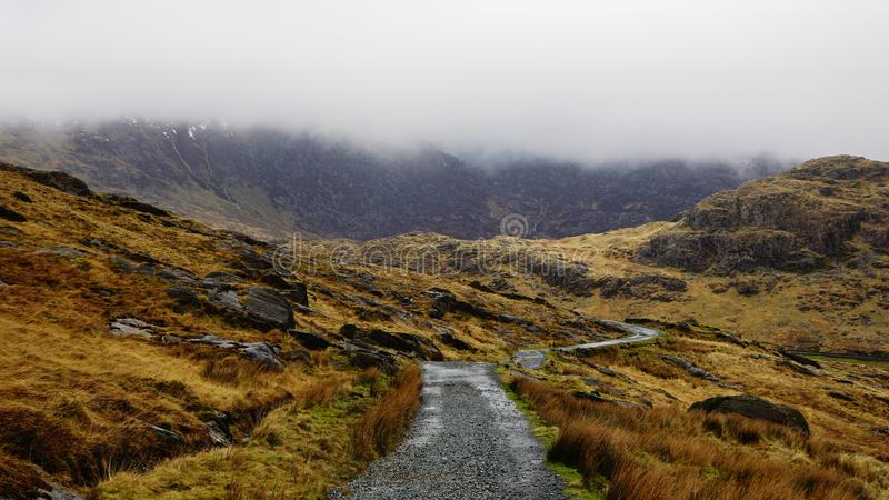 Snowdonia National Park, Wales, United Kingdom. Stone path along an impactful view, surrounded by saturated grass, beautiful mountains and a foggy sky – stock photo