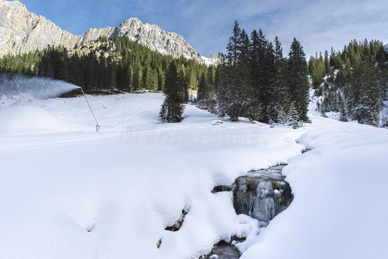 Snowdrifts near frozen creek in Austrian Alps. Winter landscape in the Austrian Alps. Frozen creek surrounded by snowdrifts and snowy pine trees royalty free stock photos