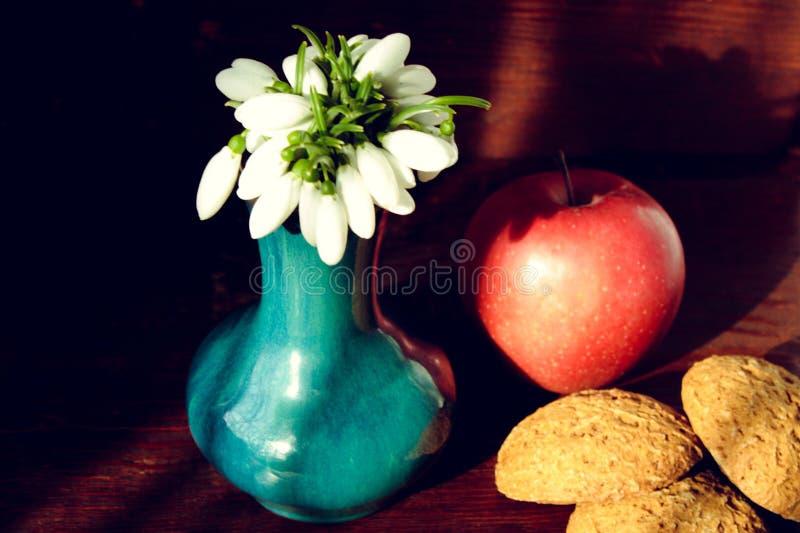 snowdrops花束在一个蓝色花瓶的用一个红色苹果和麦甜饼 库存照片