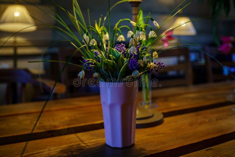 snowdrops和会开蓝色钟形花的草时髦的花束在一块陶瓷花瓶玻璃在咖啡馆的设计师内部 库存图片