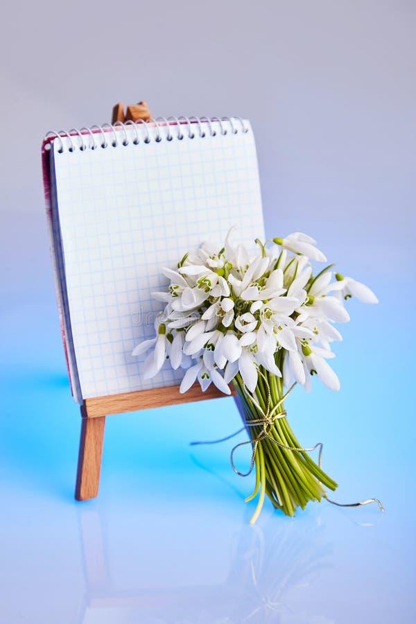 snowdrops花束和有一个笔记本的一个小画架在蓝色背景 免版税库存图片