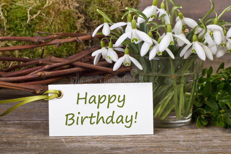 Happy Birthday. Snowdrops, twigs and card with lettering Happy Birthday royalty free stock photo