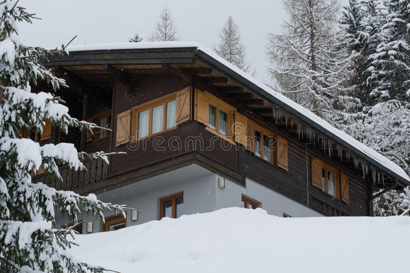 Snowed-family house in the forest. Idyllic snowed house with icicles in the woods stock photo