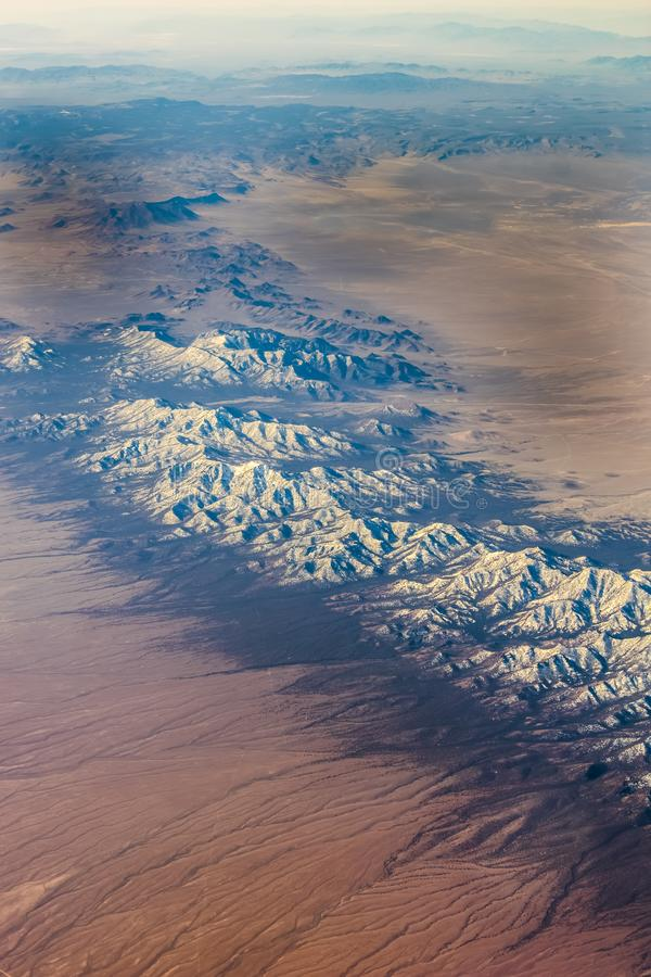 Snowed mountains with desert roads. Flying between colorado and california with snowed mountains desert, roads and rivers to the sides during spring around April stock image