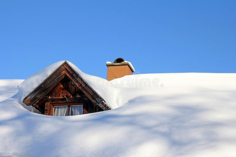 Snowed roof window of an old wooden house. A snowed roof window of an old wooden house royalty free stock images