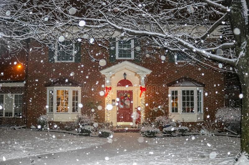 Snowfall on beautiful brick house with columns and bay windows with Christmas tree light up and red sled and wreath on porch.  royalty free stock images