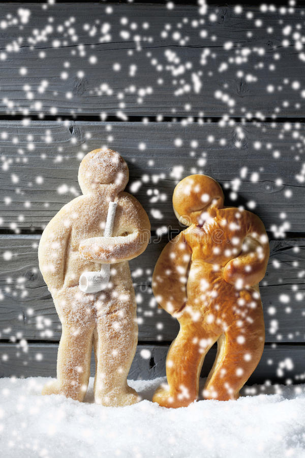 Snowfall with christmas gingerbread men on heap of snow against wooden background stock image