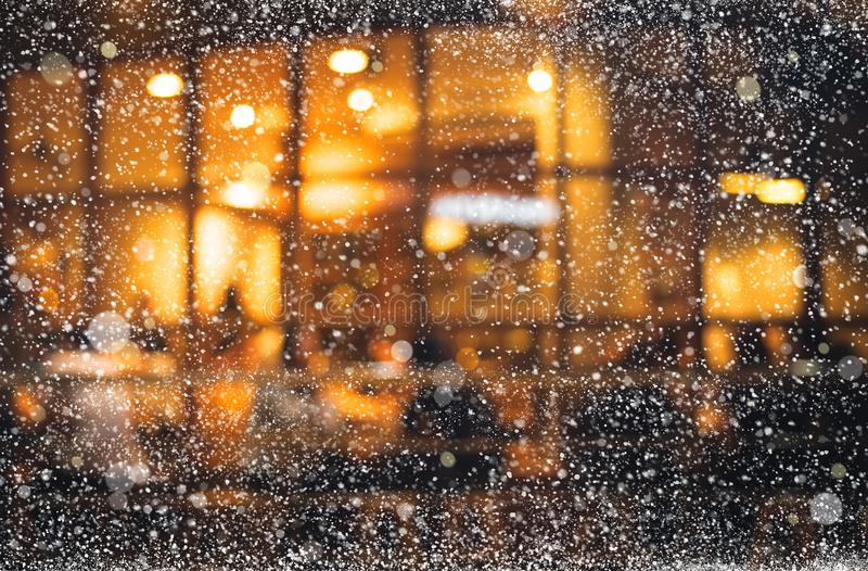 Snowfall on light bokeh of cafe restaurant in night winter. Background for holiday,christmas festive and new year concept stock image