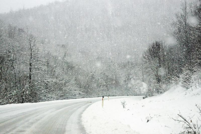 Snowfall on the road in the mountain forest. stock photos